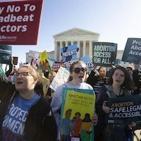 Des personnes avec des pancartes manifestent devant la Cour suprême américaine.