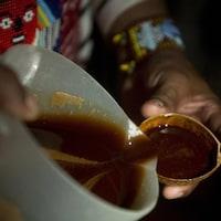 De sa main droite, un guérisseur verse de l'ayahuasca, un liquide brunâtre, dans une petite tasse.
