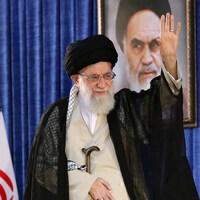 L'ayatollah Khamenei, sur une tribune, fait un geste de la main.