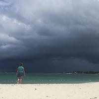 Une femme regarde les nuages noirs sur la plage d'une île des Bahamas.