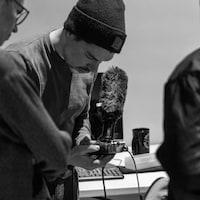 Un formateur tenant un micro, penché sur son son enregistreuse.