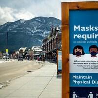Une pancarte disposée sur une rue de Banff indique que le port du masque et la distanciation physique sont obligatoires.