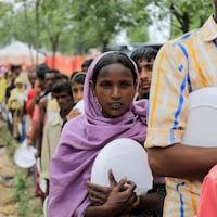 Des réfugiés ronhingyas font la queue pour recevoir de la nourriture dans un camp installé au Bangladesh.