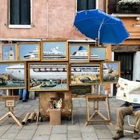 Un homme est assis, le visage couvert par un journal, à côté d'un ensemble de tableaux représentant un paquebot.