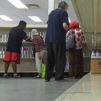 Des gens prennent des conserves sur des étagères.