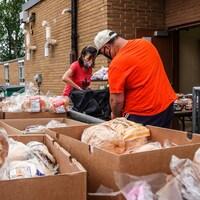 Une bénévole donne des denrées alimentaires à une personne.
