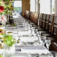 Une longue table de banquet avec ses couverts et de nombreuses chaises alignées les unes à côté des autres.