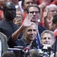 Un homme au milieu d'une foule sourit et salue la foule d'un geste de la main.