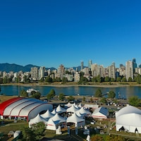 Plusieurs tentes de différents formats au bord de l'eau avec la ville de Vancouver et des montagnes en arrière-plan.