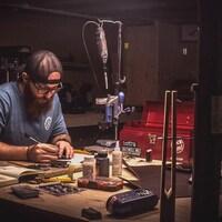Sébastien Landry est assis et mesure des morceaux de fer dans son atelier.