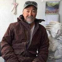 Un homme inuit vêtu d'une casquette et d'une veste pose devant l'une de ses sculptures représentant une femme.