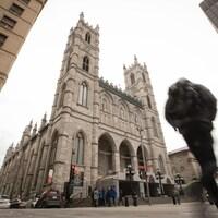 Vue de la basilique Notre-Dame, alors qu'un piéton passe devant.