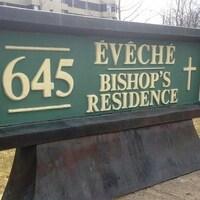 Le panneau d'accueil de l'évêché avec le numéro d'immeuble.