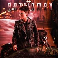 La femme aux cheveux courts porte un manteau de cuir et est assise sur une moto.
