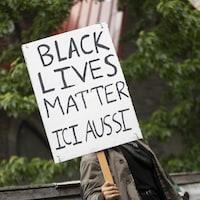 Une pancarte sur laquelle est écrit : Black lives matter ici aussi.