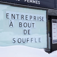 """Devanture de commerce avec une affiche où il est inscrit """"Entreprise à bout de souffle""""."""