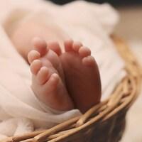 Les pieds d'un bébé sortent d'une couverture au bout d'un berceau.