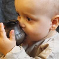 Un bébé boit du lait dans un biberon.