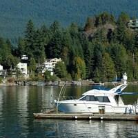 Des maisons en arrière-plan autour d'un lac et en avant-plan un bateau  à quai.