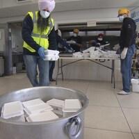 Plusieurs bénévoles, portant des turbans, des masques et des gants, dans une cuisine communautaire, mettent de la nourriture dans des boites blanches et les placent dans un grand conteneur.