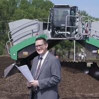 Un homme se tient debout en souriant devant de la machinerie destinée à l'aération du compost.
