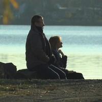 Le couple, assis sur le bord de l'eau, regarde au loin.