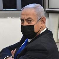 Benyamin Nétanyahou, assis dans une salle, le visage masqué, les bras croisés.