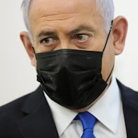 Benyamin Nétanyahou porte un masque et regarde du coin de l'œil.