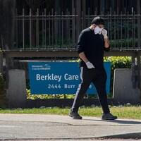 Un homme porte un masque et marche à l'extérieur du centre de soins Berkley, à North Vancouver.