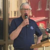 Charles Bernard parle dans un micro devant les journalistes.