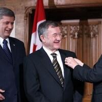 La sénatrice Marjory LeBreton remet l'épingle du Sénat à Bert Brown, en présence de Stephen Harper, le premier ministre de l'époque.