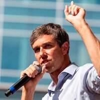 Beto O'Rourke tient un micro dans une main et lève l'autre main vers le ciel