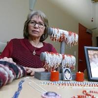 Betty Rourke est assise derrière une table où se trouvent de nombreux bracelets sur un présentoir et des photos de femmes.