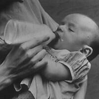 Un bébé dans les bras d'une femme qui lui donne le biberon.