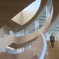 Un homme monte les marches d'un escalier en bois de la nouvelle bibliothèque centrale de Calgary.