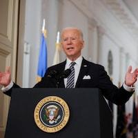 Joe Biden, les bras ouverts, est devant un micro, à côté d'un drapeau américain et sous un lustre