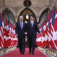 Joe Biden et Justin Trudeau marchent côte à côte au milieu d'une rangée de drapeaux canadiens et américains.