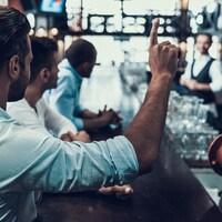 Une photo d'un homme tentant d'attirer l'attention d'un barman en levant la main au bar.