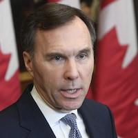 Plan rapproché de M. Morneau, devant des drapeaux du Canada.