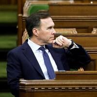 Bill Morneau est assis à la Chambre des communes.