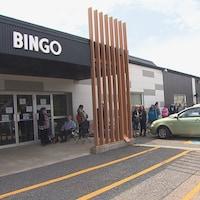 File de personnes devant une salle de bingo en été.