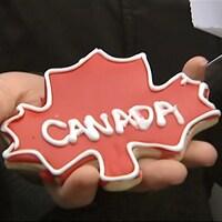 Biscuit en forme de feuille d'érable avec le mot Canada écrit en glaçage dans la main d'une jeune femme.