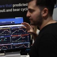 Deux hommes discutent face à un écran qui montre les cours de cryptomonnaies.