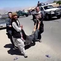 Des hommes transportent un corps dans la rue.
