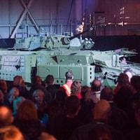 Une foule regarde un char d'assaut.