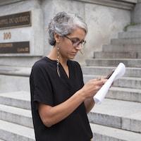 Mme Manaï écrit sur son téléphone, devant la Cour d'appel du Québec.