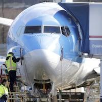 Un travailleur se tient sur une plateforme près de l'avion.