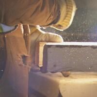Un travailleur tient une planche de bois dans une scierie.