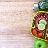 Une pomme, une bouteille et un contenant réutilisable avec des aliments
