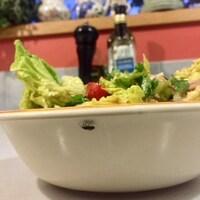 Un insecte se balade sous le rebord d'un bol de salade, devant une bouteille d'huile et une poivrière.